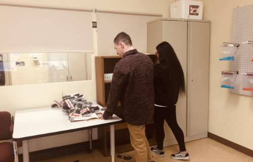 Two students organizing the supplies onto the shelf
