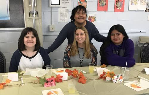 Staff with three students at the feast