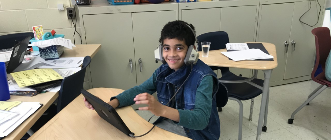 Student working in class on the Chromebook with headphones on