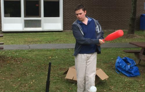 Student swinging the baseball bat
