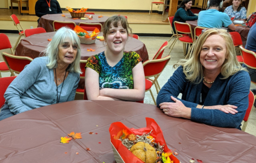 Two staff members and one student at table during Thanksgiving Feast