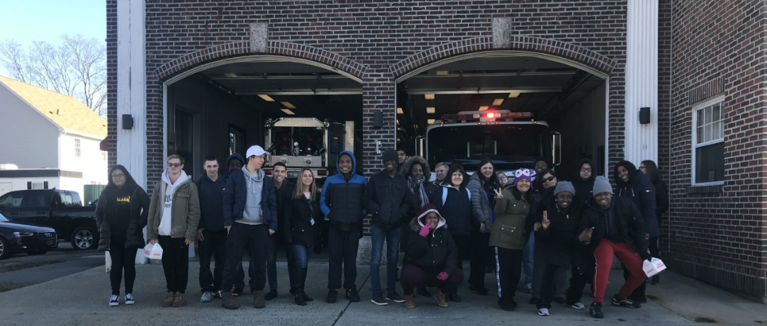 Firemen and students in front of the station