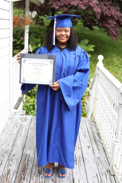 graduate in commencement gown holding diploma