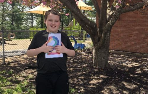 student outside by three holding 2