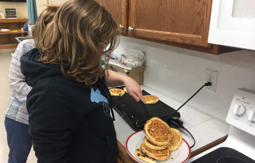 Student with a stack of pancakes