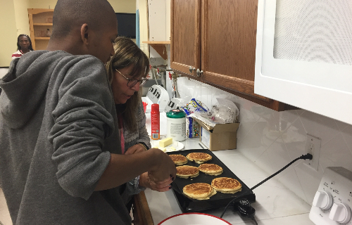 Student and staff making pancakes