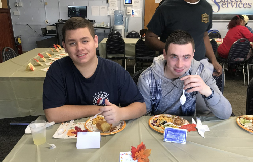 Two students at Thanksgiving Feast with a full plate of food