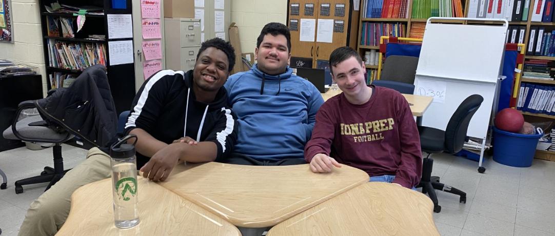 Three students sitting at the desks