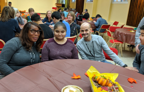 Students and staff at table during Thanksgiving Feast
