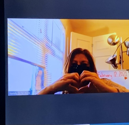 Staff member working remotely making a heart with their hands