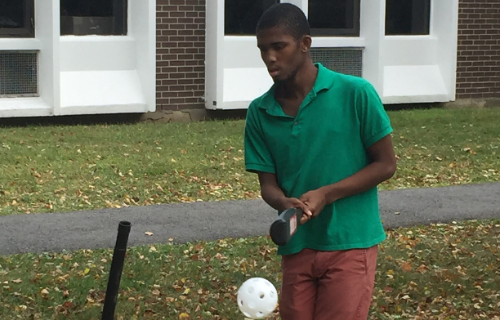 Student playing baseball outside in gym class