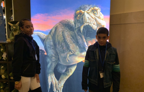 Students at museum posing in front of another exhibit
