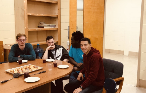 Several students at table waiting to eat the hot dogs
