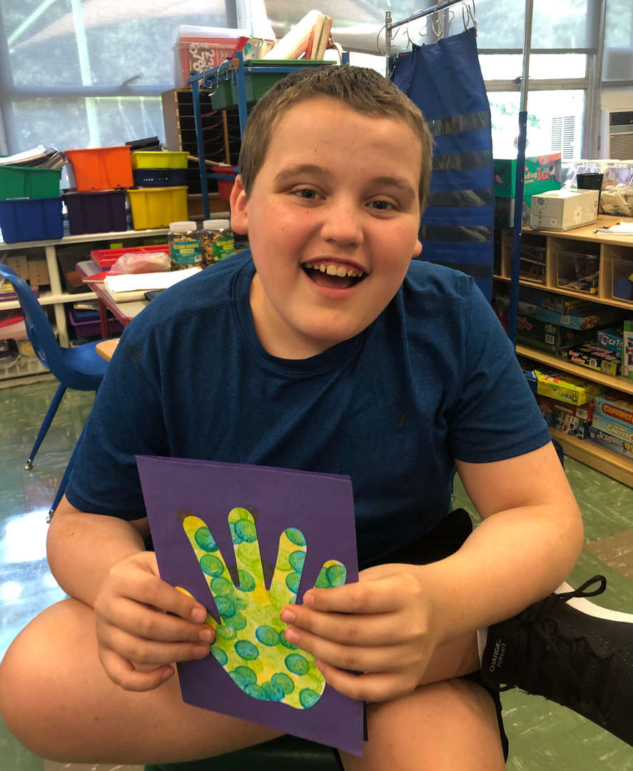 A boy holds up a card decorated with a painted paper handprint.