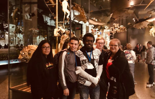 Students and staff smiling and posing at the  Museum of Natural History