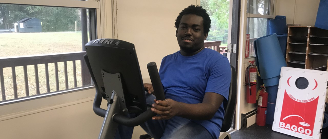 Student in Gym working out on the exercise bike