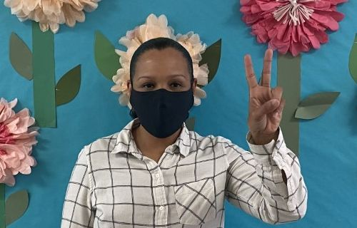 Speech teacher in building wearing a mask signng number one.