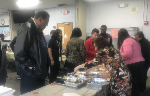 Staff and students at the feast filling their plates