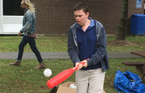 Student playing baseball as the ball is pitched