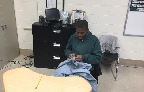 Student folding a blue shirt