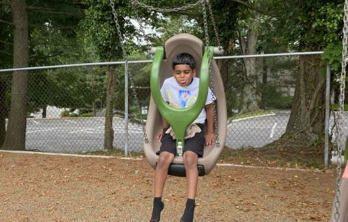 Boy happily swinging.