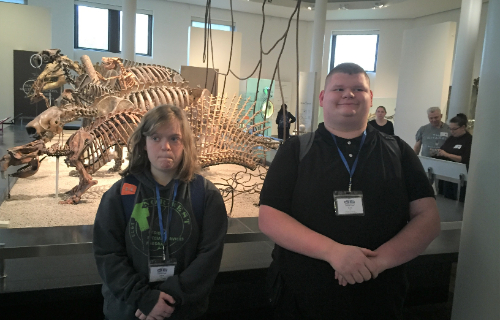 Two students at Museum with Dinosaur Bones