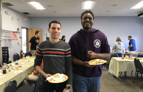Students standing at Thanksgiving Feast with their plates