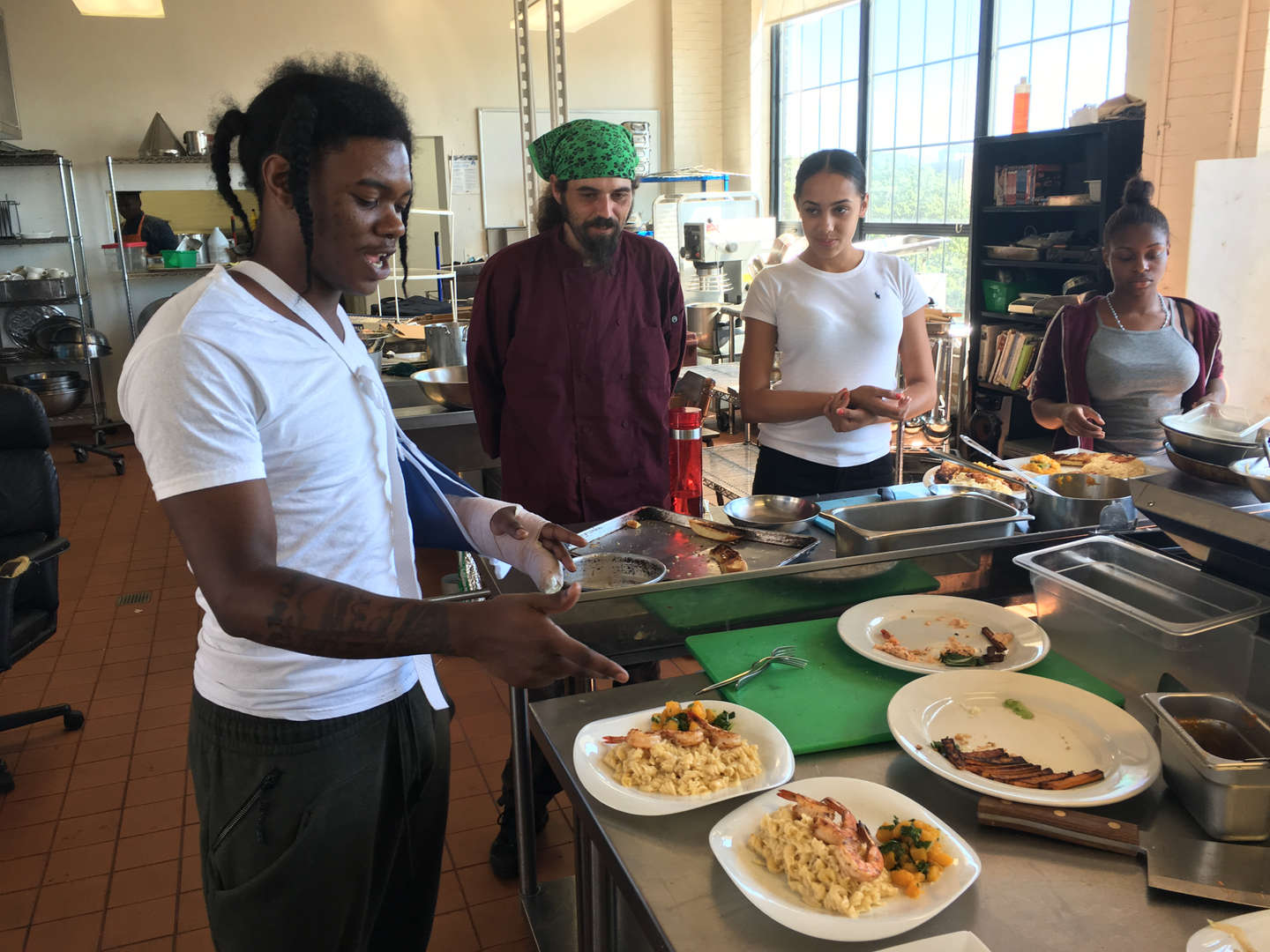 Culinary student Savian Eugene explains his dish to Chef.