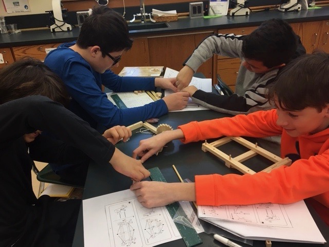 STEM 7 students are working in small groups to build da Vinci designs as part of the course engineering unit.