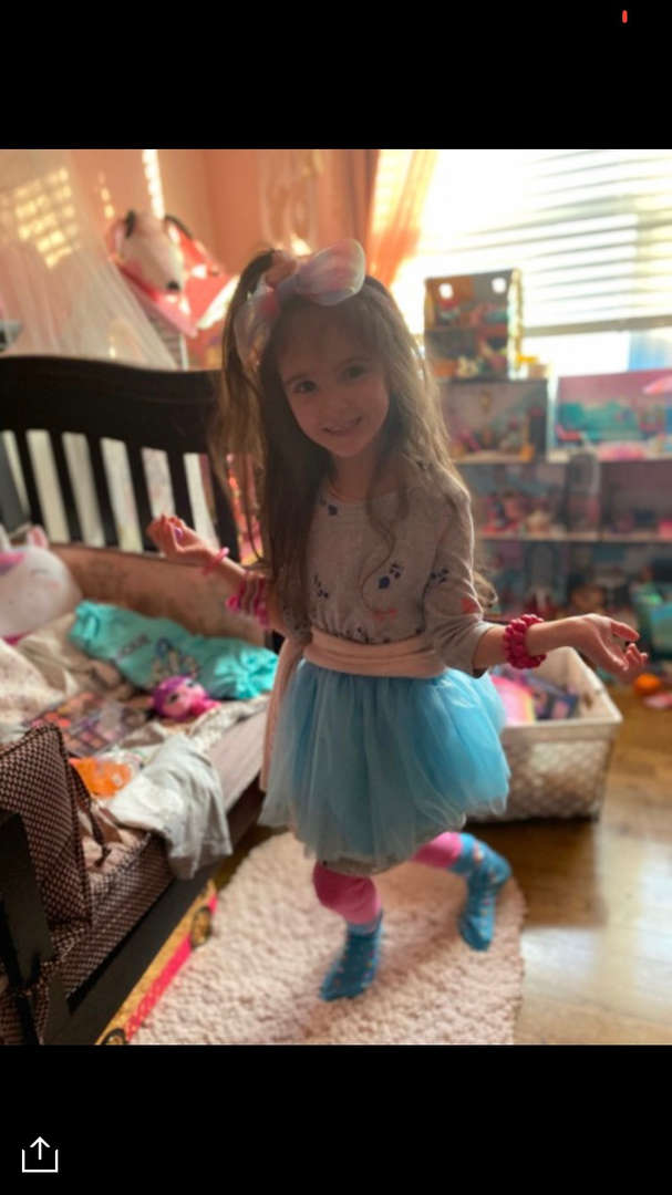 a girl in a blue tutu with a big bow in her hair