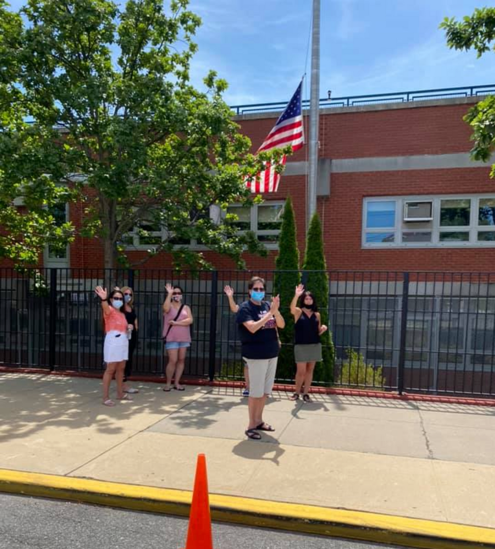 a group of the staff clapping at the passing cars of 5th graders
