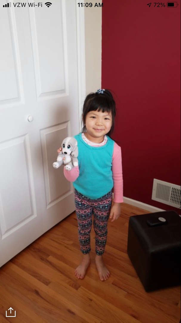 A cute girl holding her stuffed puppy