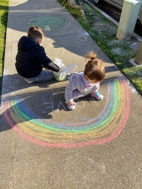 a brother and sister drawing rainbows with chalk outside on a driveway