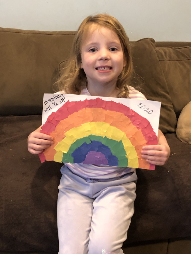 A 1st grader holding her picture of a rainbow