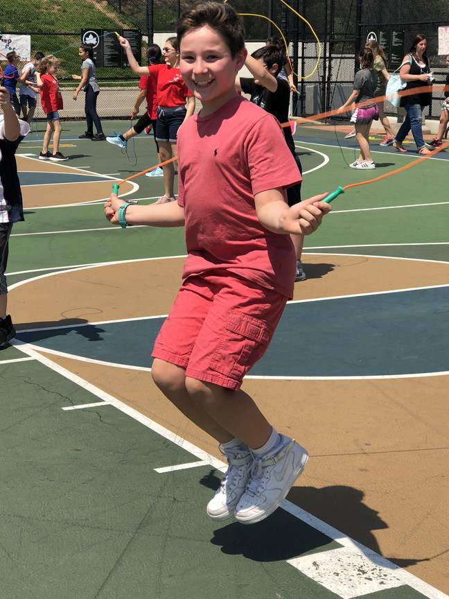 a boy jumping rope with a big smile on his face