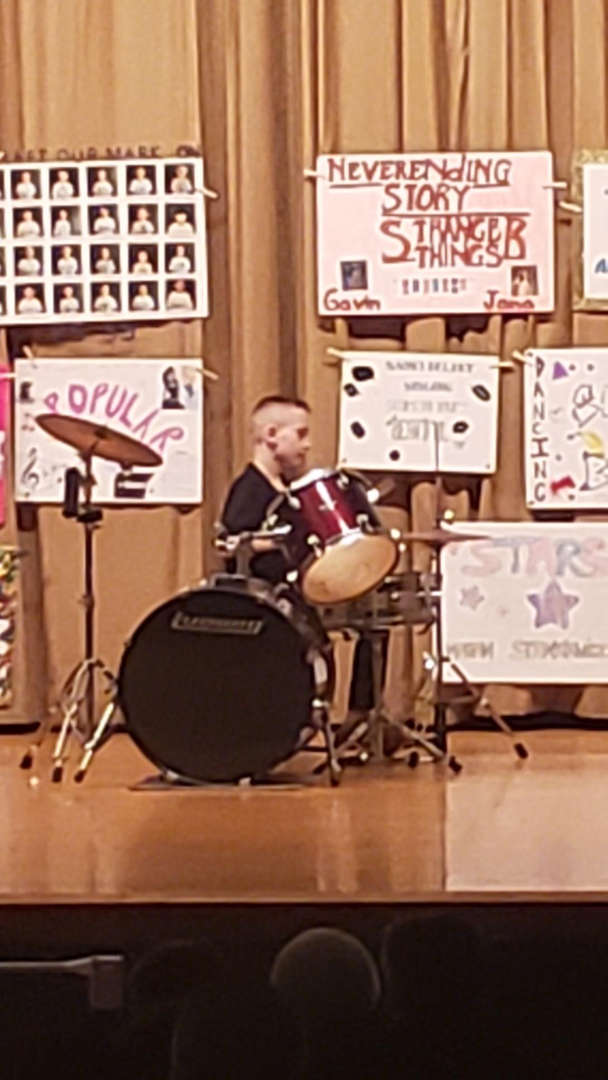 a boy playing a full set of drums