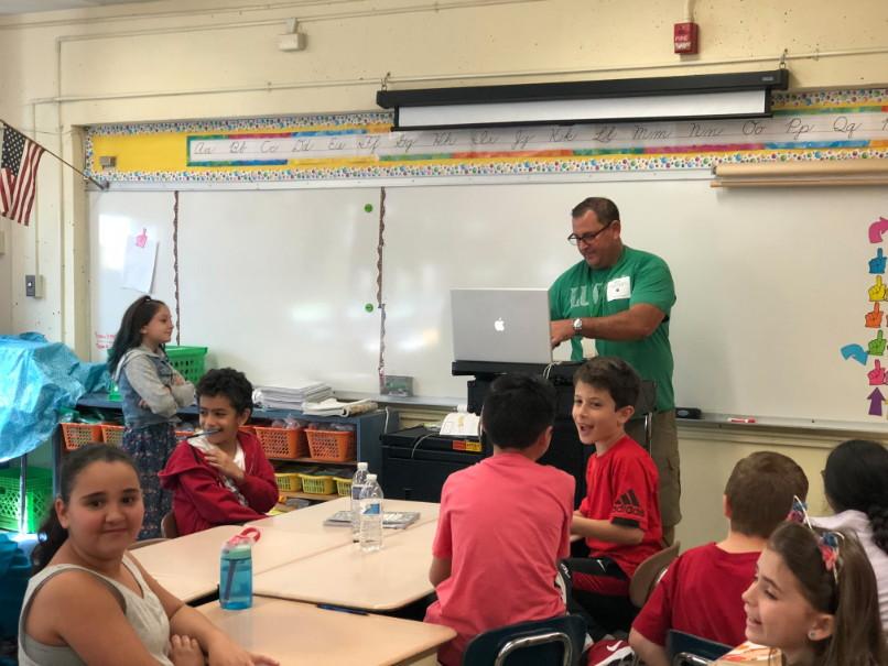 a man in a green tee shirt preparing to speak