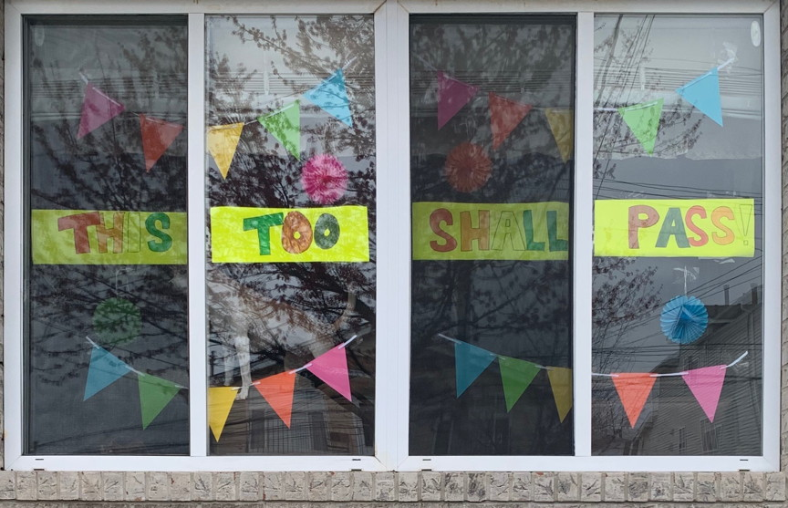 sign in a window that says This Too Shall Pass!