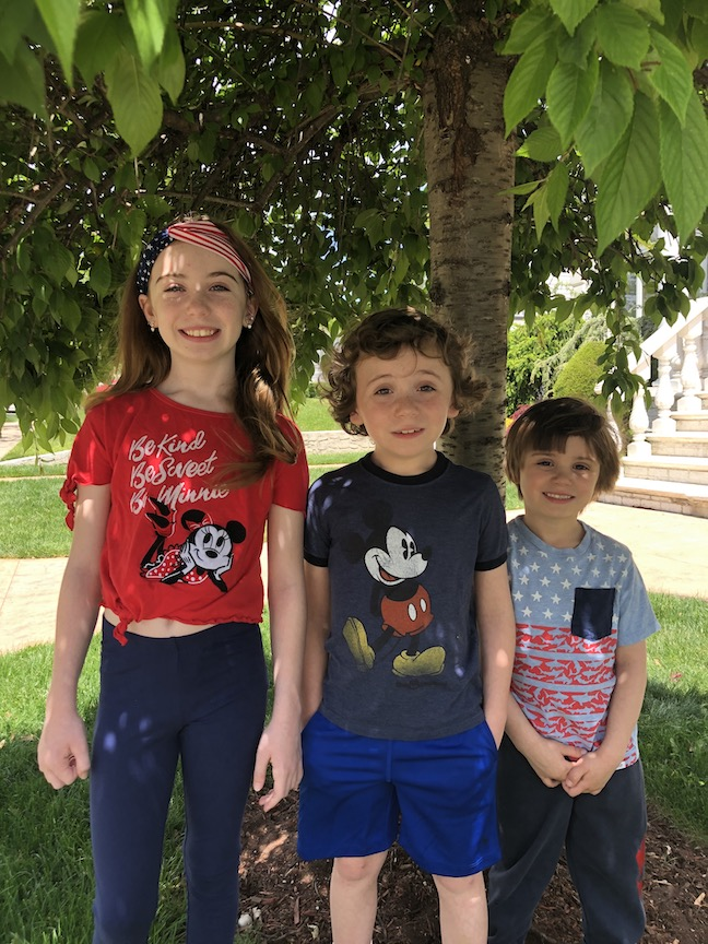 A sister and two brothers are wearing their patriotic tee-shirts