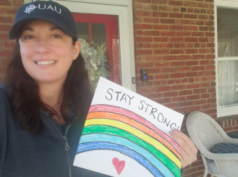 Teacher  holding her rainbow picture in front of her house