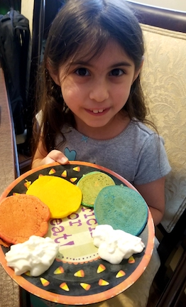 this girl has a plate of different colored cookies