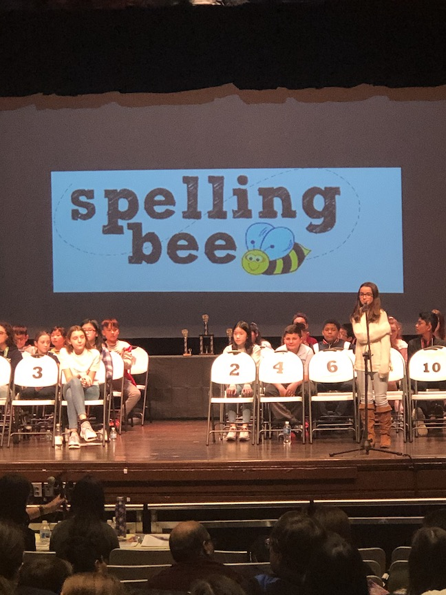 The stage of the spelling bee with children seated on the stage