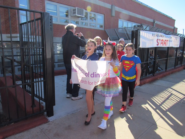 children marching out of the gate holding a banner