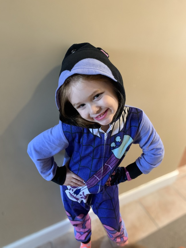 This adorable girl is wearing a one piece costume with a hood