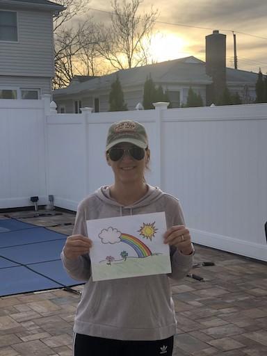 teacher in a baseball cap showing her rainbow