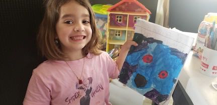 a girl showing the hero book she made