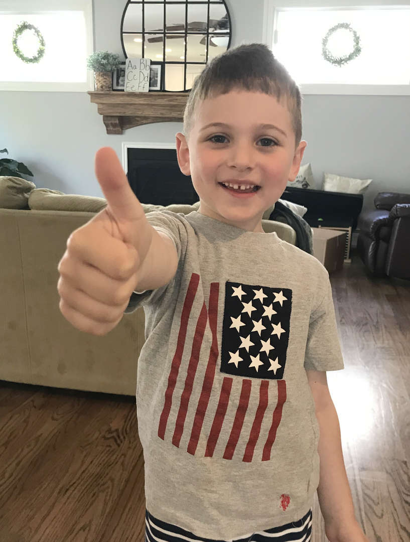 This boy has a thumbs up for his American flag tee shirt