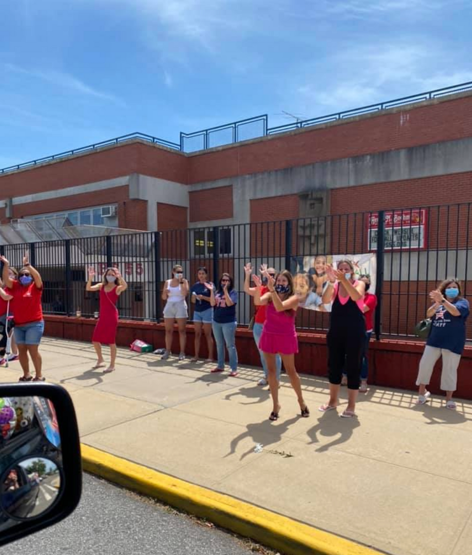another group of teachers waving to the 5th graders