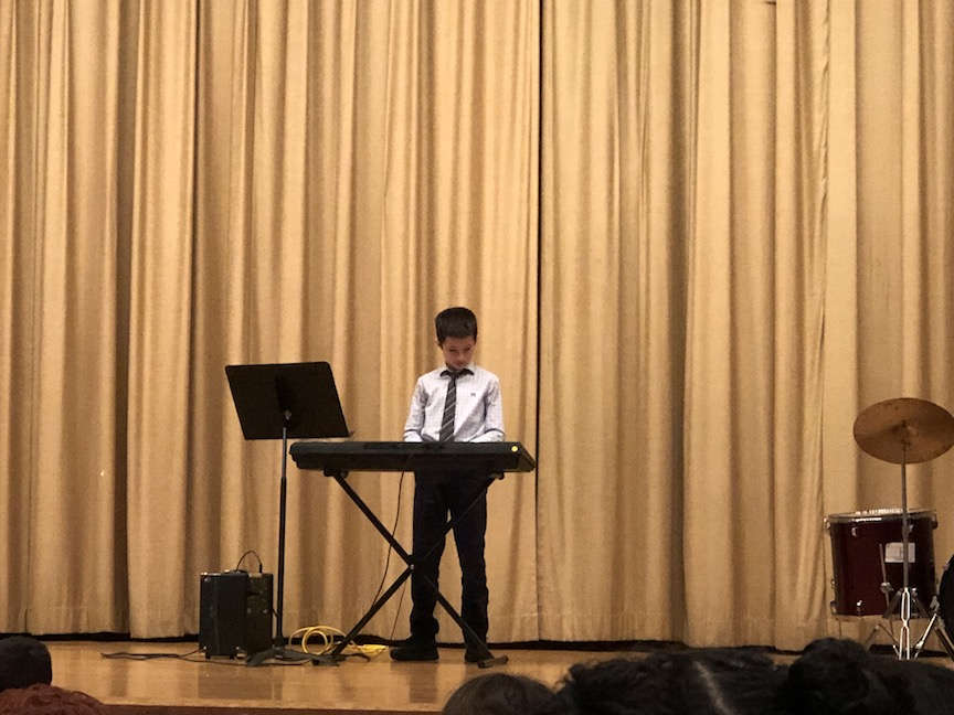 a boy playing the keyboard
