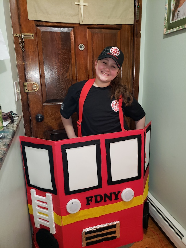 this girl is dressed as a firefighter and made a firetruck to wear. It looks like she is driving it!